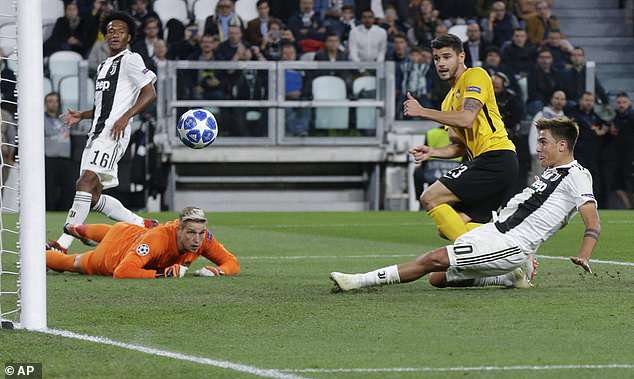 Juan Cuadrado (left) watches on as his cross is tapped into an empty net by Dybala