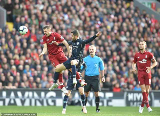 James Milner (left) goes up for a challenge with Bernando Silva as Jordan Henderson watches on in the first half