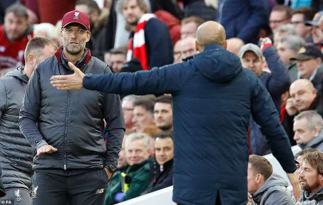 Guardiola debates an incident with Liverpool manager Jurgen Klopp (left) as the action continues on the pitch