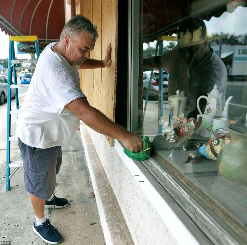 Bobby Smith boards up the windows at Jani's Ceramics in Panama City, Florida on Monday in preparation for the arrival of Hurricane Michael