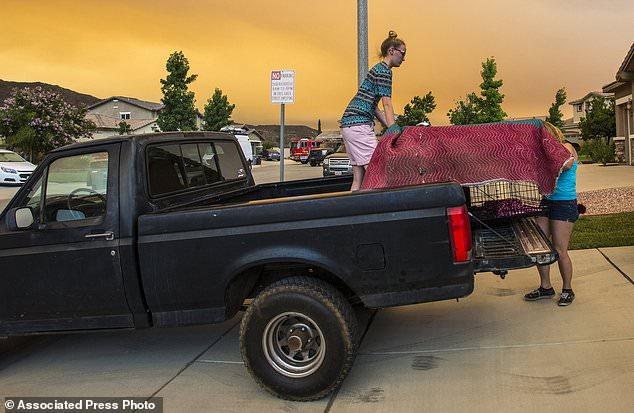 Bewohner am Crystal Ridge Court in Lake Elsinore, Kalifornien, laden einen Lastwagen, als sie evakuieren, während das Heilige Feuer am Mittwoch, den 8. August 2018, in der Nähe ihres Hauses brennt. (Mark Rightmire / Das Orange County Register via AP)