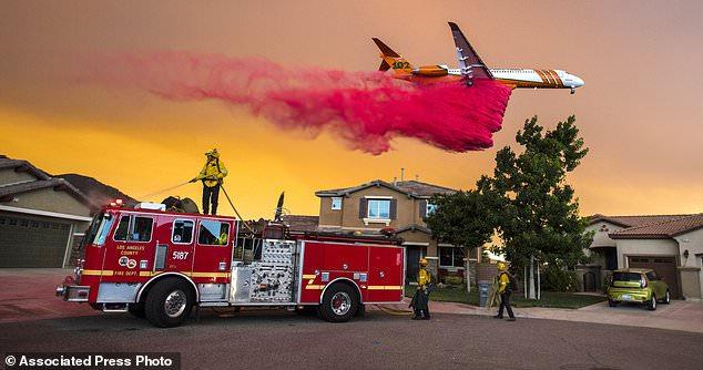 Ein Flugzeug fällt feuerverzögernd hinter Häusern entlang McVicker Schlucht-Park-Straße in See Elsinore, Calif., Während das heilige Feuer am 8. August 2018 in der Nähe von Häusern brannte. (Mark Rightmire / The Orange County Register über AP)