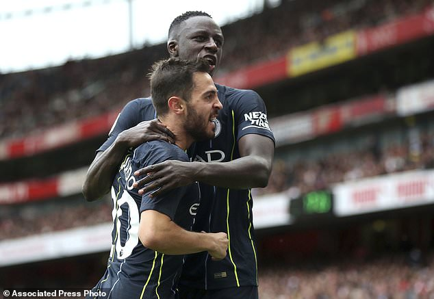 Manchester City's Bernardo Silva, left, celebrates with Benjamin Mendy after his team's second goal during the English Premier League football match between Arsenal and Manchester at the Emirates Stadium, London. Sunday, August 12, 2018. (Nick Potts / PA via AP)