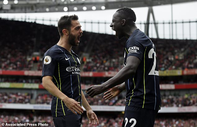 Manchester City Bernardo Silva celebrates with his teammate Benjamin Mendy, right, after his team's second goal during the English Premier League football match between Arsenal and Manchester City at the Emirates Stadium in London, England, Sunday, August 12, 2018. (AP Photo / Tim Ireland)