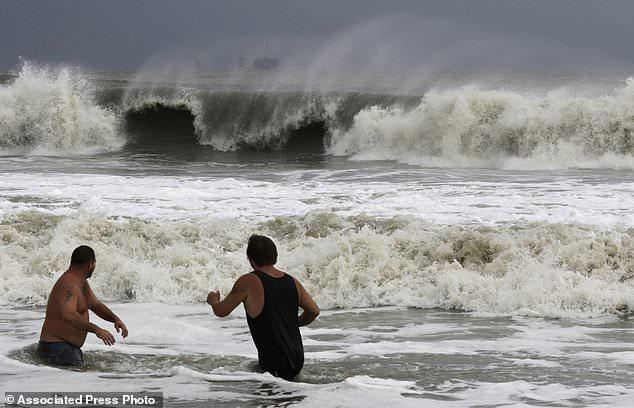 John Cunningham, links, und Hunter Shows, rechts, beobachten die Wellen von Tropical Storm Gordon am Dienstag, 4. September 2018, in Dauphin Island, Ala. (AP Foto / Dan Anderson)