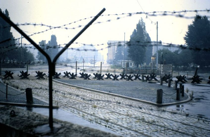 The view of Potsdamer Platz in 1962 looking along Leipziger Strasse, which is where the East Berlin tram can just be made out. Off-camera to the left is the site of Hitler's bunker. Although Westerners could approach the Berlin Wall up to any distance, East Berliners were kept beyond a control zone which extended approximately up to the position of the tram. The 'X' shaped constructions are tank traps. When this shot was taken, from the West, the Berlin Wall was still made of crude blocks topped with barbed wire. Later it was replaced with a more solidly built barrier. The site the photographer is standing on is now the five-star Ritz-Carlton hotel