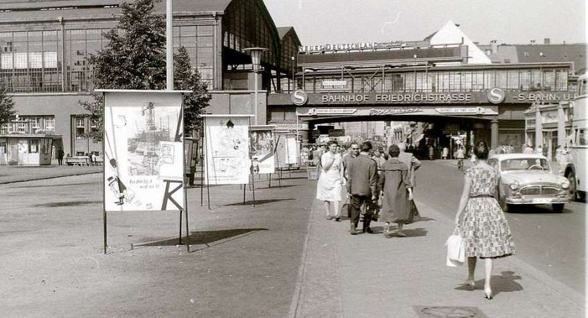 Friedrichstrasse Station pictured on September 12, 1959. The station, in the east of the city, was, and remains, one of the principal railway stations of Berlin serving both the S-Bahn and U-Bahn. During the period of the Berlin Wall, it was the main rail connection to and from the West for non-Germans, who were subject to strict controls when entering or leaving the East. At the time of this shot, anyone could travel by rail or on foot between the two sectors of Berlin while undergoing few, if any, formalities. An advertisement for Neues Deutschland, the principal communist daily newspaper, can be seen on the railway bridge, and the ubiquitous political slogan boards are also in evidence