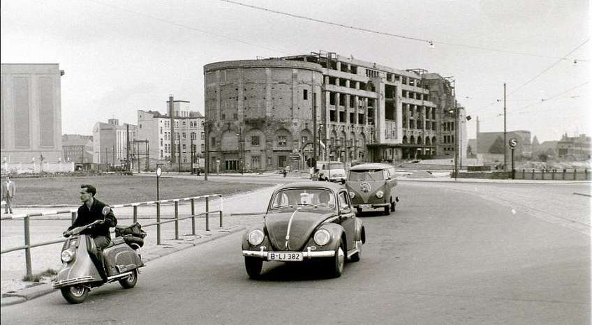 Potsdamer Platz in East Berlin in August 1960 before the Berlin Wall was built. This faces west in the days when traffic moved freely between West and East Berlin. The Volkswagen vehicles bear West Berlin licence plates. In the background is the ruined Haus Vaterland (Fatherland House), which lay on Eastern territory, with Stresemannstrasse off to the left. Potsdamer Platz and the border with West Berlin is off-camera to the right. Haus Vaterland, built in 1928, was a major entertainment centre housing among other attractions Cafe Piccadilly, the largest cafe in the world. It was demolished in 1976