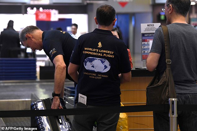 Passengers wearing commemorative T-shirts place their luggage on the scales to be weighed at Changi Airport