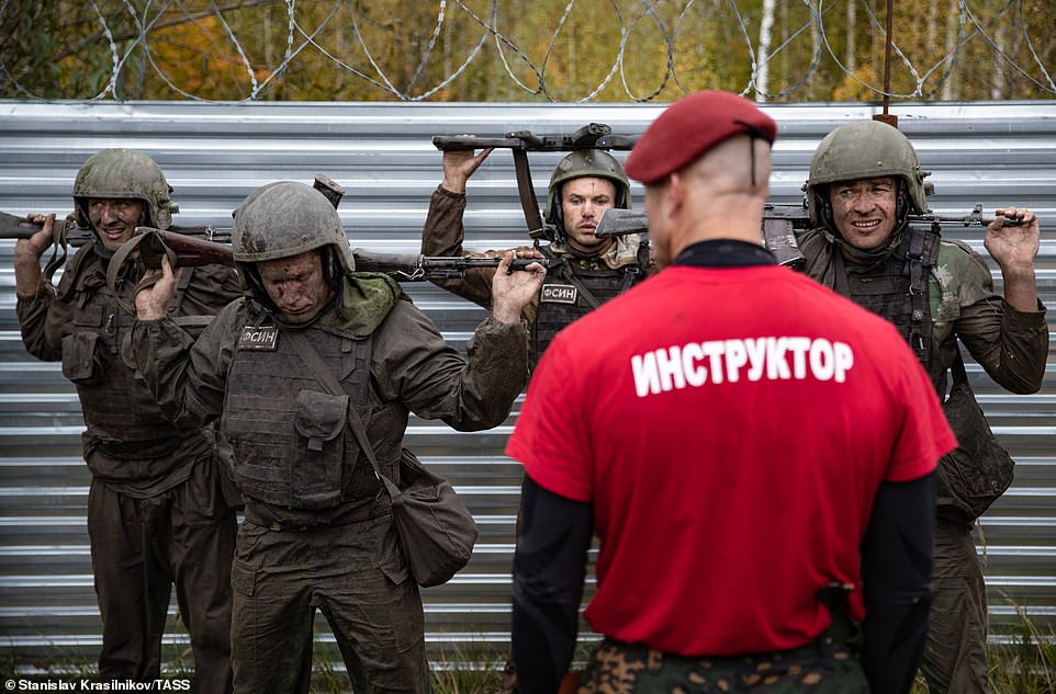 A strapping soldier with a maroon beret puts the contenders through their paces beside a barbed wire fence