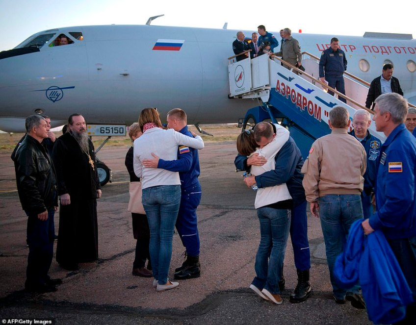 Alexey Ovchinin (center left) of Roscosmos, and Flight Engineer Nick Hague (center right) of NASA, embrace their families after landing at the Krayniy Airportin Baikonur, Kazakhstan after their aborted mission