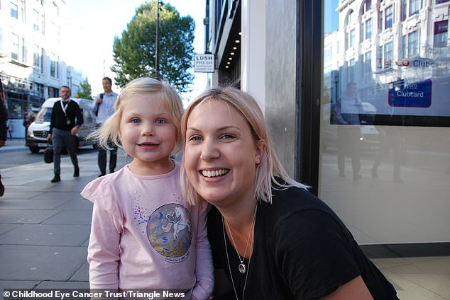 Alice's mother Emily (pictured) noticed she could not see out of her left eye when she covered the other with an eye patch. She fought for Alice to keep her eye, thinking she would be grateful  as a teen. They are pictured at the launch of a childhood eye cancer trust campaign