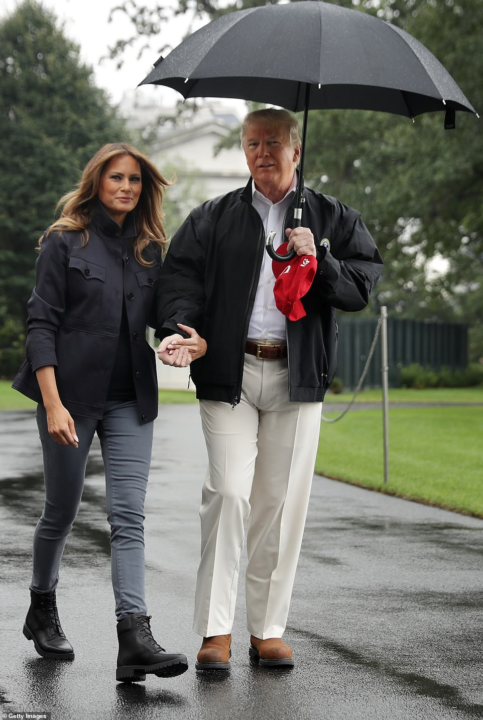 Even when the couple were together, the umbrella was nowhere near Melania who was left soaking as the rain came down
