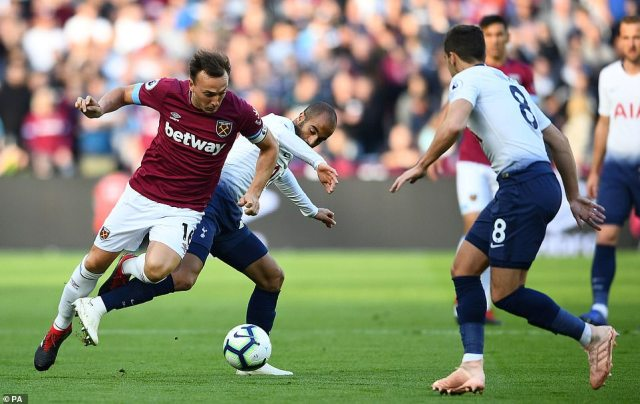 West Ham captain Mark Noble goes down under the challenge of Lucas Moura (centre) in the first half of action