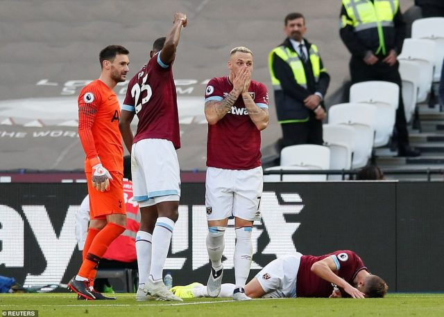 Andriy Yarmolenko (right) lies on the floor in agony asMarko Arnautovic (No 7) can't bear to look as play is stopped