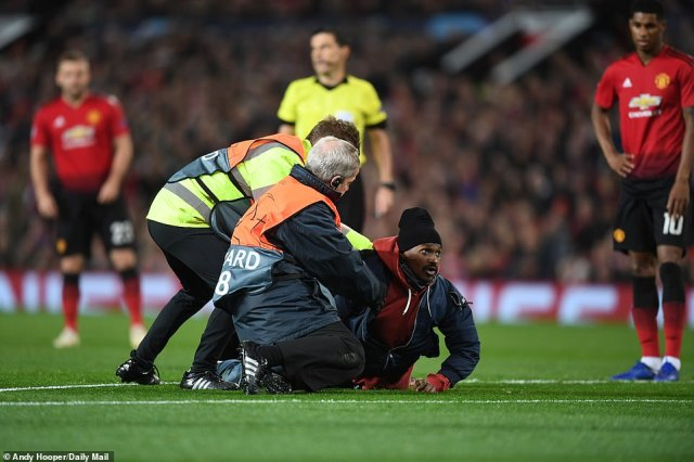An intruder was brought to his knees by stewards after racing onto the Old Trafford pitch during the first few minutes