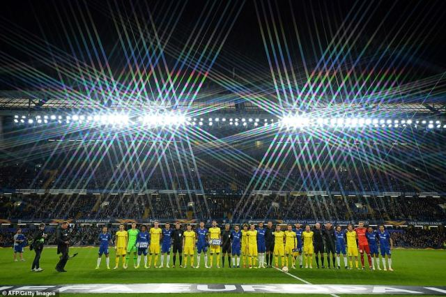 The two teams line up under the floodlights at Stamford Bridge prior to kick-off in the Europa League group-stage match