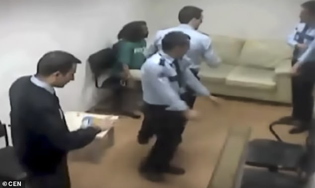 Brown was handcuffed to a chair, but manages to escape in less than a minute - and that's when officers tackle her to the ground and hold her down