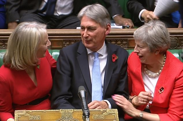 Liz Truss (left) and Prime Minister Theresa May (right) congratulate Philip Hammond as he finishes making his budget statement