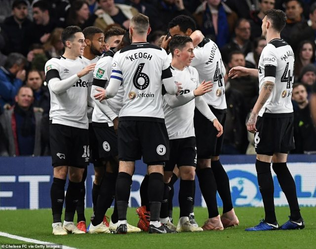 Marriott is surrounded by his Derby team-mates after bringing them level within four minutes of falling behind in the  clash