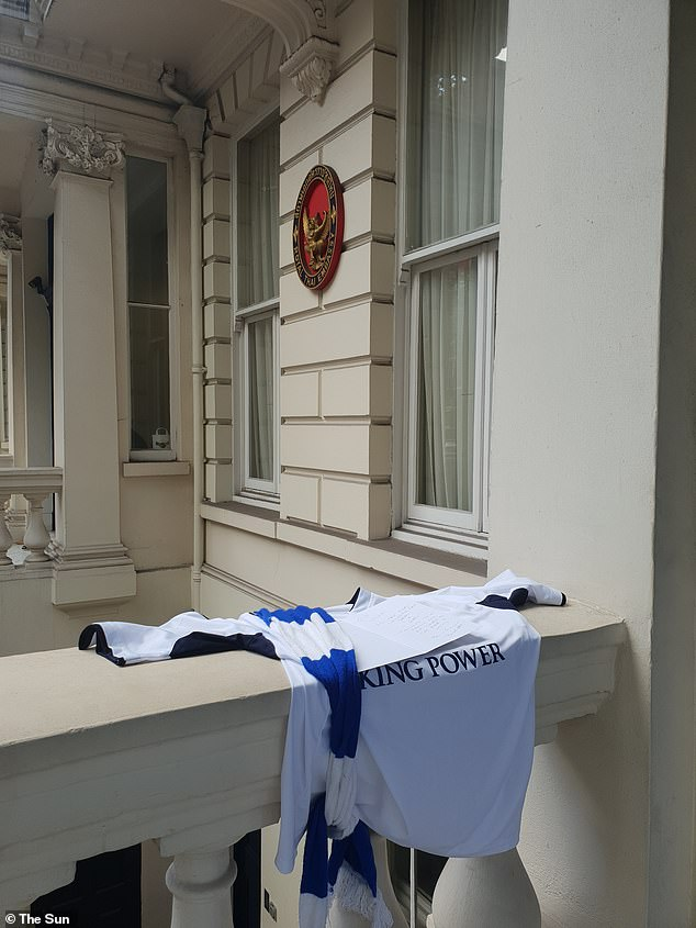Tribute: A fan had left the club shirt and scarf outside the embassy with a handwritten note on top