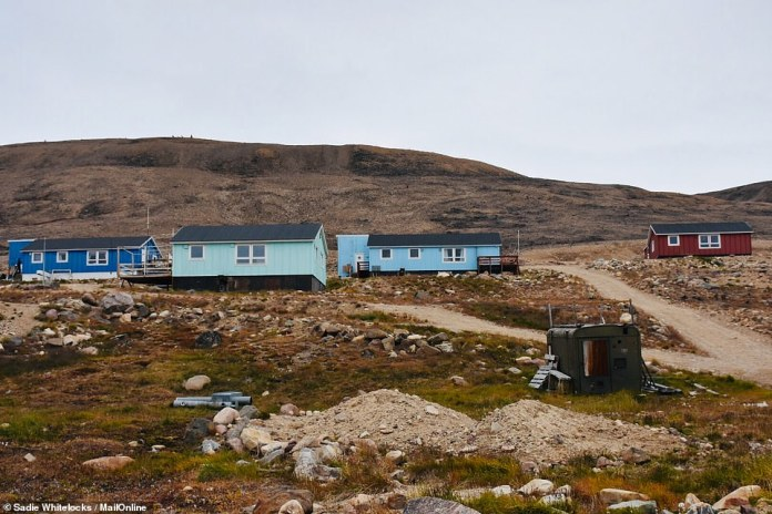 The colorful houses in Qaanaaq are characterized by the rugged landscape