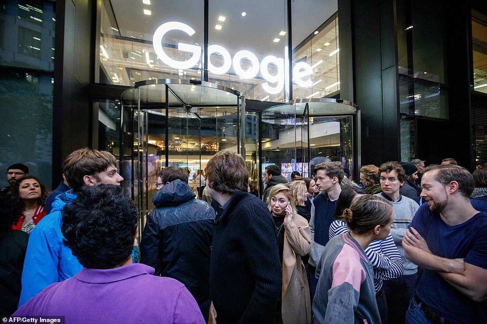 A woman is seen talking on her phone as people talk and mingle preparing for the Google walkout in London on Thursday