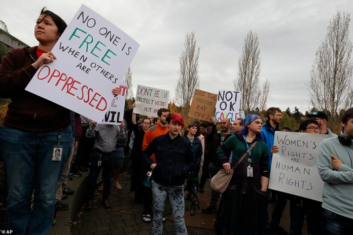 "Google employees in Seattle, Washington wear signs saying, ""Nobody is free when others are oppressed"" and ""Has the payoff been worth it?"" during the Global Walkout on Thursday"
