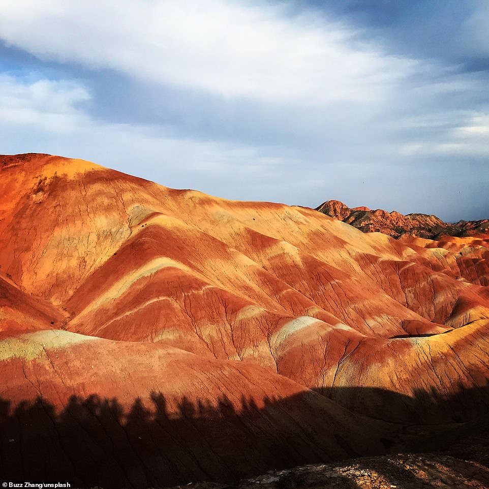 The colorful mountains of Zhangye National Geopark near the Chinese border with Mongolia. Sandstone and mineral deposits have created the swirling orange, yellow and white moonscape