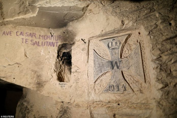 """Graffiti of an anonymous soldier in Latin and blue ink reads: """"Hello Caesar, we who die will greet you"""""""
