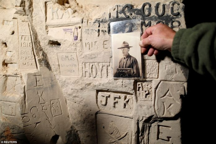 Gilles Chauwin, president of the Chemin des Dames Association and a lover of World War I, shows a portrait of American soldier F. A. Hoyt of the 26th Infantry Division alongside graffiti he left behind in the 12-mile tunnel complex 100 years ago. Mr. Chawin's historical union could compare Hoyt's service protocol with his graffiti in the tunnel. He survived the war
