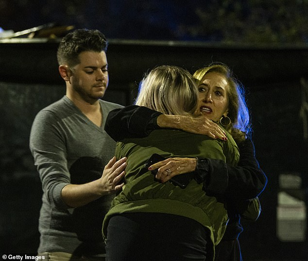 Matthew Rodin, left and Susan Turner comfort Melissa Hutchinson who rendered aid to some of the victims of a mass shooting