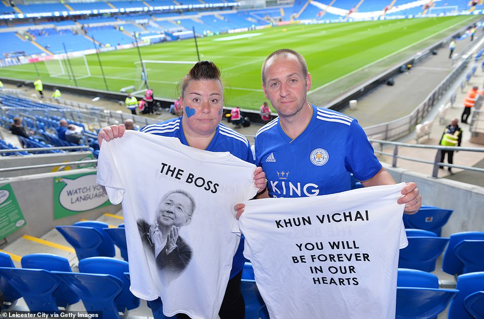 Fans of Leicester City hold special tribute T-shirts in honor of the deceased chairman of the club high before they compete against Cardiff