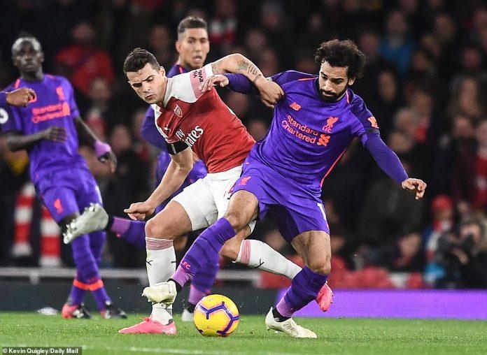 Salah (right) fights Arsenal midfielder Granit Xhaka in the first half at the Emirates stadium