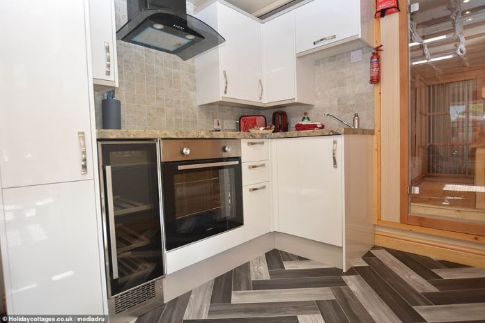 The fully equipped kitchen has an oven, stove, wine cooler and fridge. On the right, a door leads into a sauna