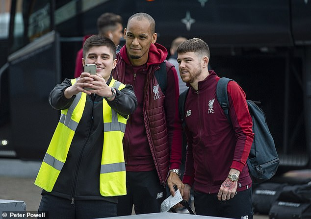 An airport worker takes a selfie on Monday with Liverpool duo Fabinho and Alberto Moreno