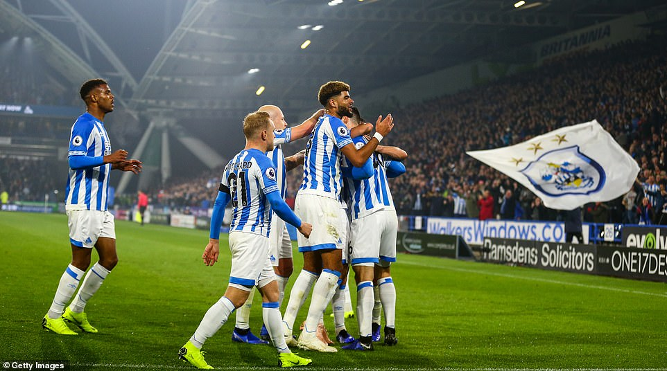Schindler is under attack by his cheering team-mates after playing a crucial role in Huddersfield's first home goal of the season
