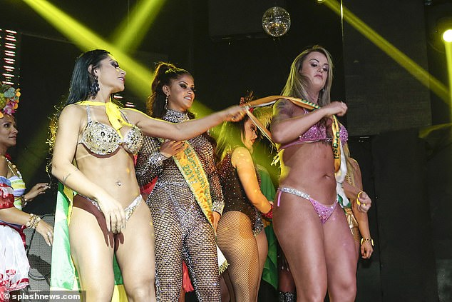 Ms Santana (left) tries to take her winner's sash back as Ms Uva (right) flaunts her figure, she later claimed she was the only '100% natural' contestant
