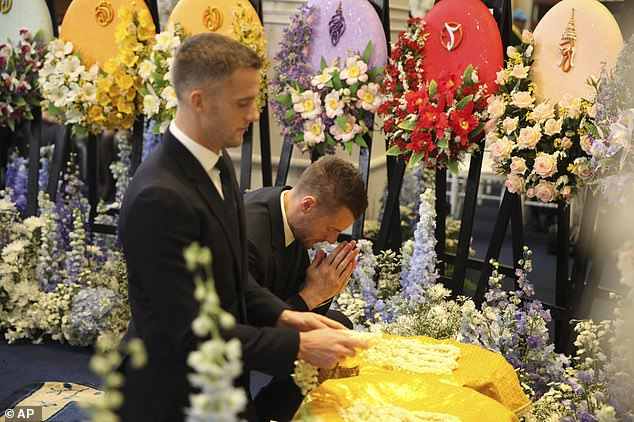 Striker Jamie Vardy (right) is pictured praying after offering a floral tribute to his late bossSrivaddhanaprabha