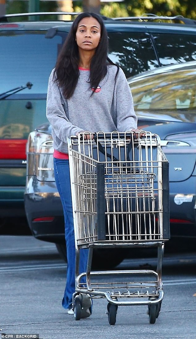 Shopping trip: Zoe was dressed in a gray sweater and blue jeans and left her long hair loose and worn with a center parting