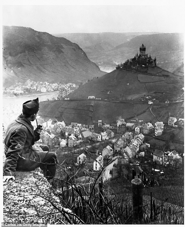 A soldier smokes a pipe and looks across the valley at the castle above the Moselle River in Cochem, Germany. The landmark was the headquarters of the Fourth Army Corps of the U.S. Army of Occupation in Germany