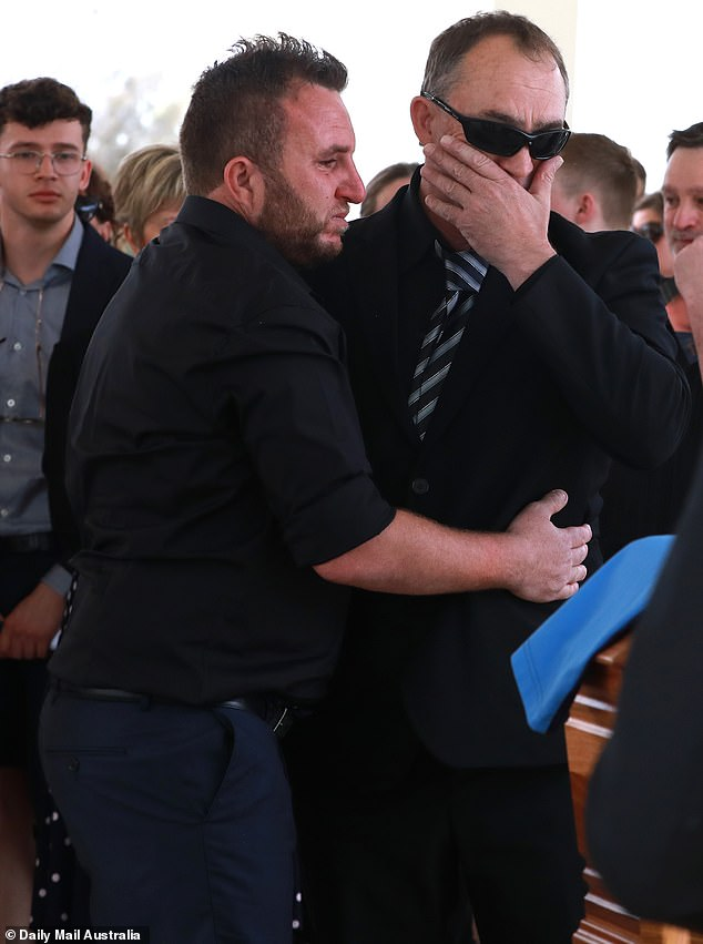 Colin Sylvia's father Craig (pictured left) is comforted after laying his son to rest on Friday in Mildura