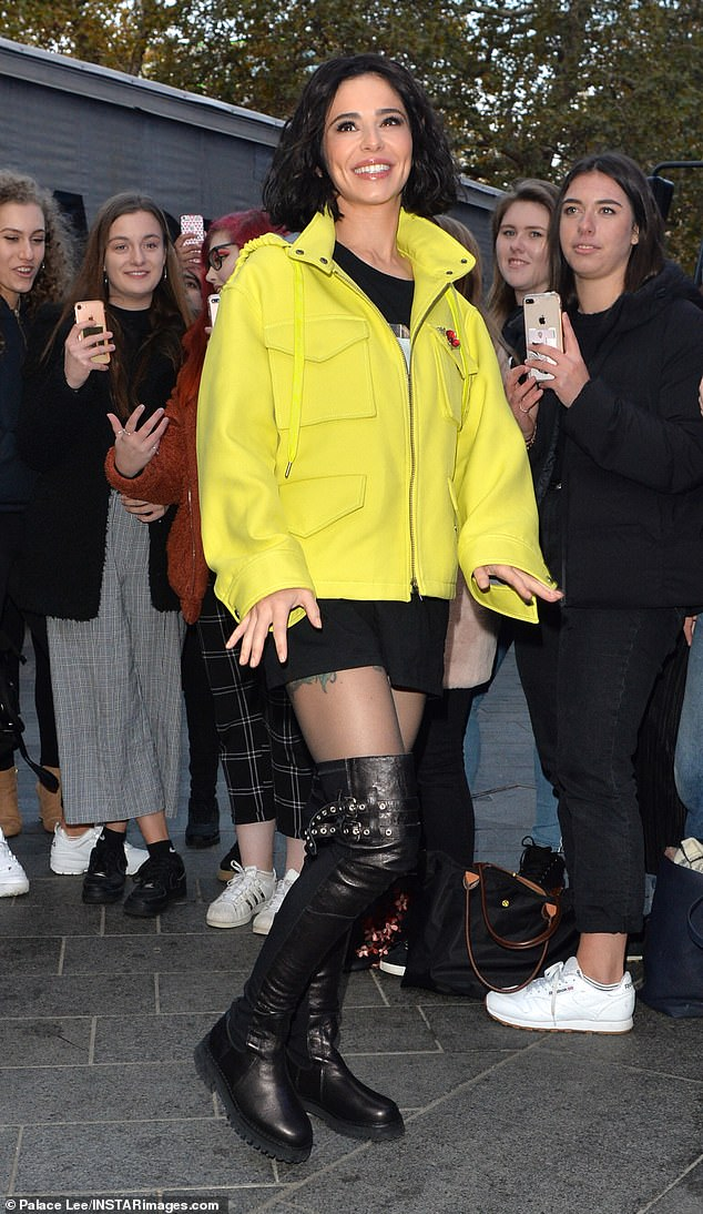 Bright: Cheryl suffered a rare fashion failure in a fluorescent yellow jacket and boots high until the climax when she arrived at the Capital radio studios in London on Friday to promote her return to the track diss.