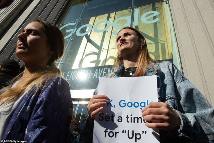"""Another protester carried a piece of paper with the words, 'OK, Google Set a time for """"Up,""""' as they walked out of the office building located in Chelsea on 8th Avenue in New York"""