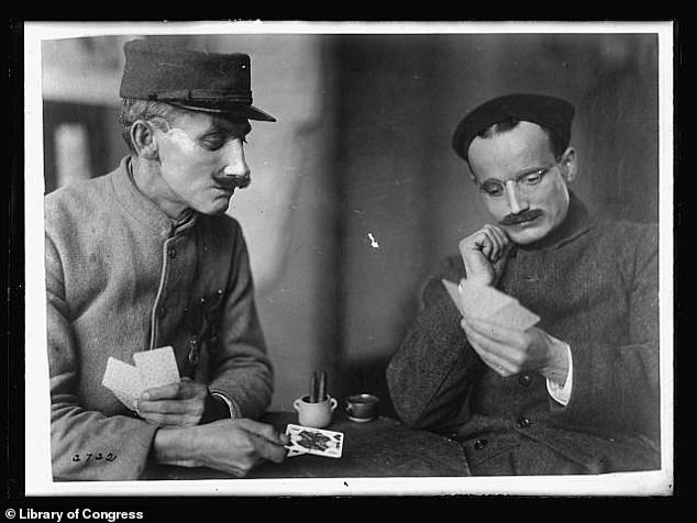 Two wounded soldiers playing cards after wearing a full denture in April 1919