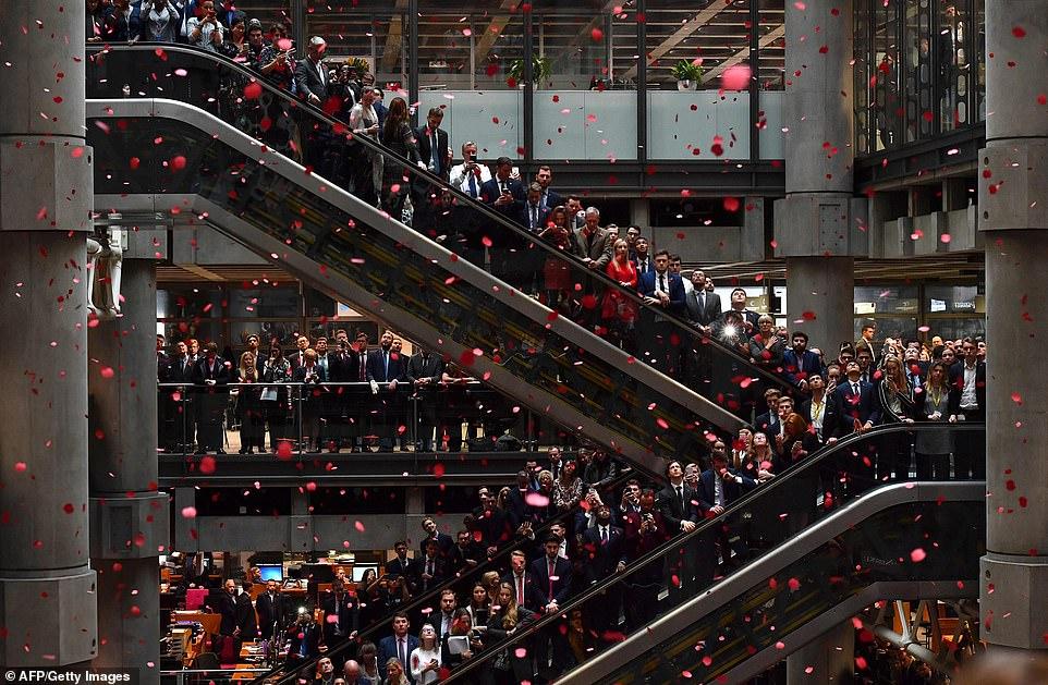 Des coquelicots rouges tournoyaient autour du célèbre bâtiment alors que les employés observaient une minute de silence en commémoration du jour du Souvenir, à l'intérieur du Lloyd's of London, sur la photo.