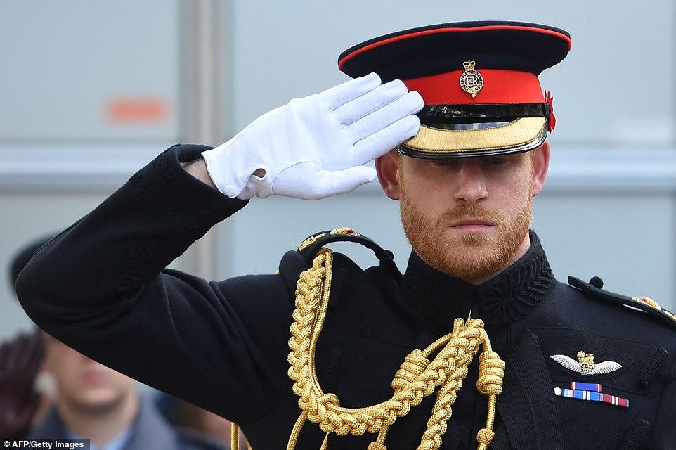 Le prince britannique Harry, duc de Sussex, salue après avoir posé une croix du Souvenir devant des croix en bois représentant les sépultures de soldats britanniques inconnus des première et deuxième guerres mondiales, lors de sa visite au champ du Souvenir à l'abbaye de Westminster