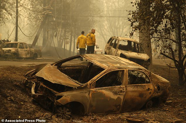 Sonoma Valley firefighters inspect burned out to be sure they are clear of human remains following fire through a neighborhood, Friday, Nov. 9, 2018, in Paradise, Calif. (AP Photo / John Locher)