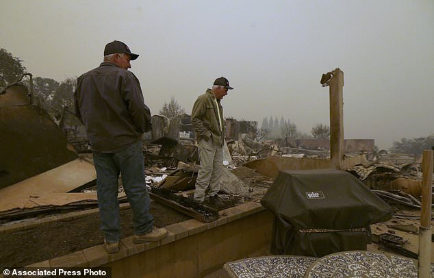 Larry Marple, right, accompanied by his son, Rod Marple, looks over the burned remains of his home, Friday, Nov. 9, 2018, which was destroyed by a wildfire that swept through the area on Thursday, in Paradise, Calif. . (AP Photo / Rich Pedroncelli)