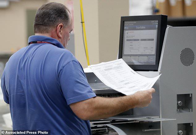 Ein Angestellter im Broward County Supervisor of Elections führt Stimmzettel durch eine Maschine. Er zählt Stimmzettel aus den Zwischenwahlen vom Donnerstag, 8. November 2018, in Lauderhill, Florida (AP Photo / Wilfredo Lee).